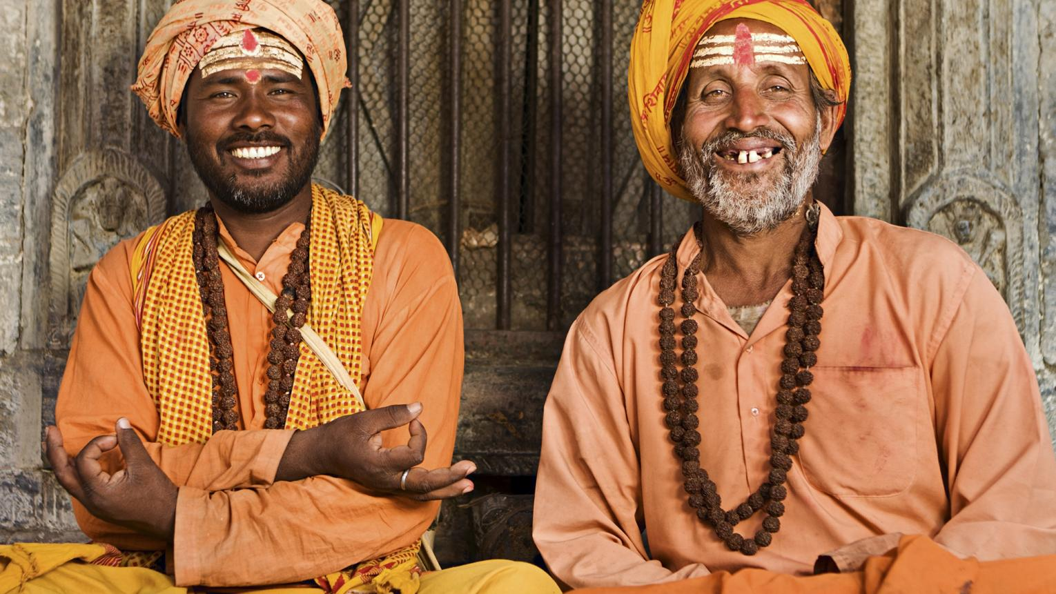 Two Indian men dressed in orange clothes socialize together.