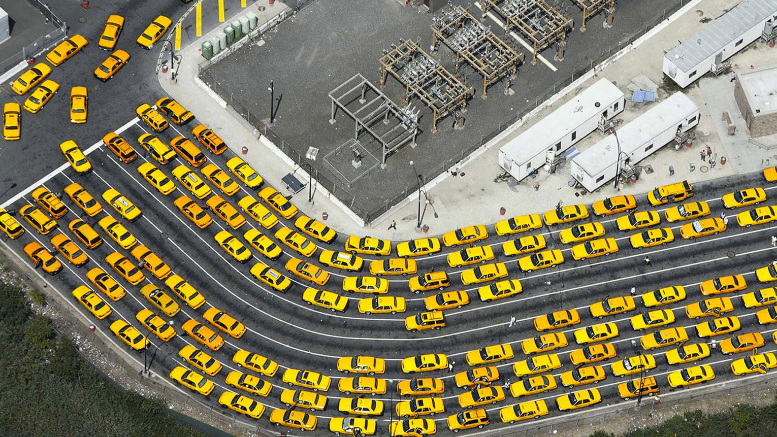 Vibrant yellow taxis stand out from grey surroundings.
