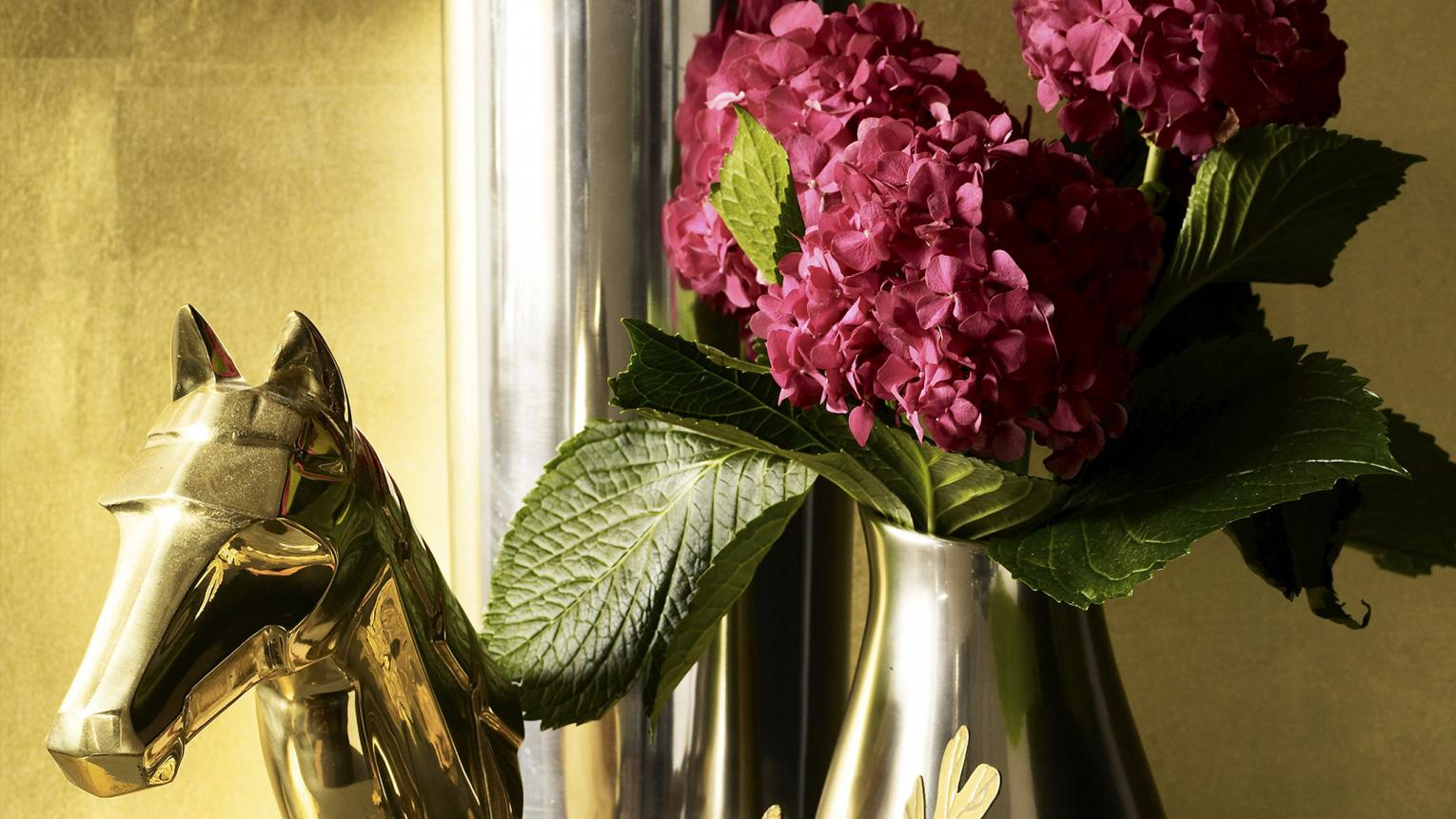 A gold vase filled with pink hydrangeas, a gold horse statue and assorted trinkets sit on a mantel piece.