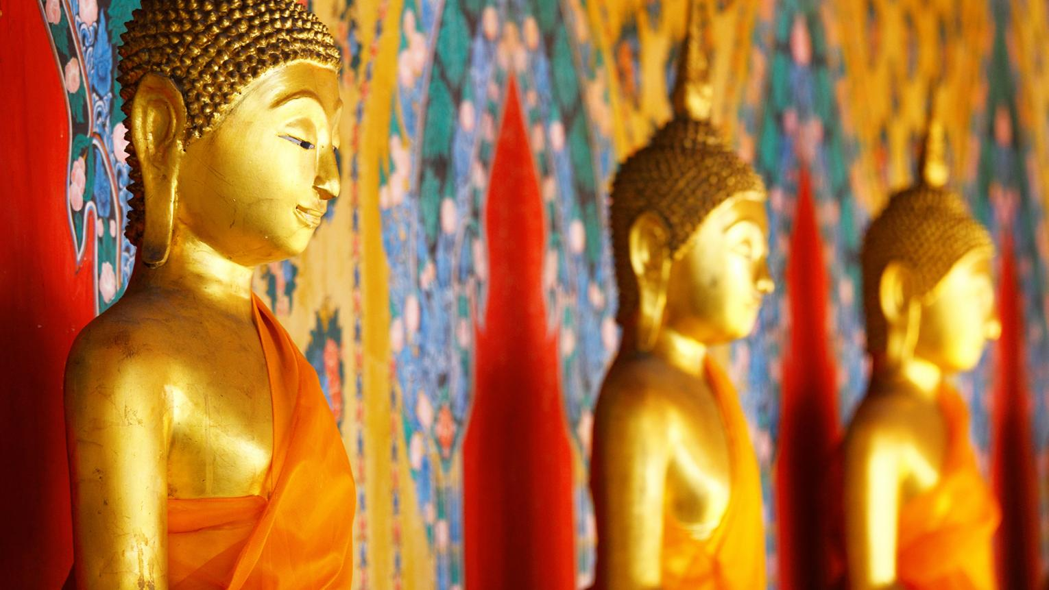 Gold Buddha statues sit against beautiful gold, red and blue material.