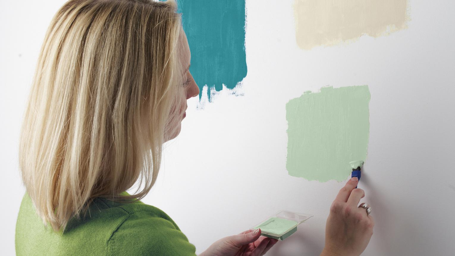 Testing green paint swatches on a wall to pick the right colour.