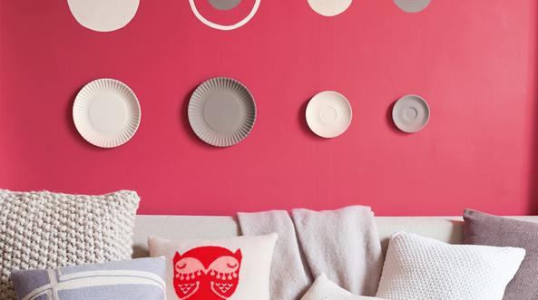Living room with circles painted on a bright coral wall.