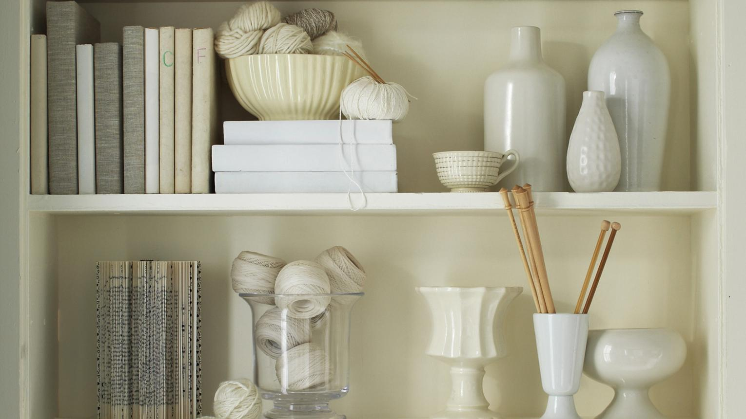 Bookshelves filled with vases, books and precious momentos in beautiful shades of white and off-white.