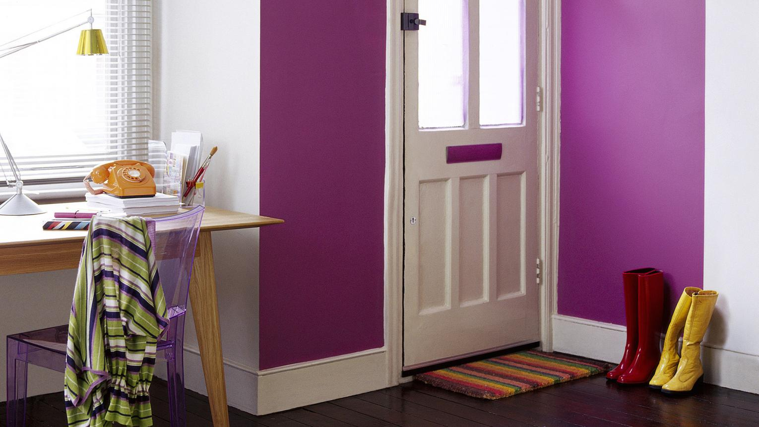 Spacious hallway decorated with a vivid violet feature wall, statement light pendant and home office.