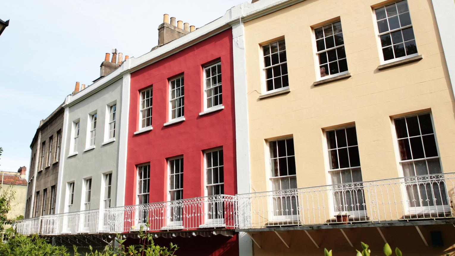 Classic paint colours show off the exterior details of a row of houses.