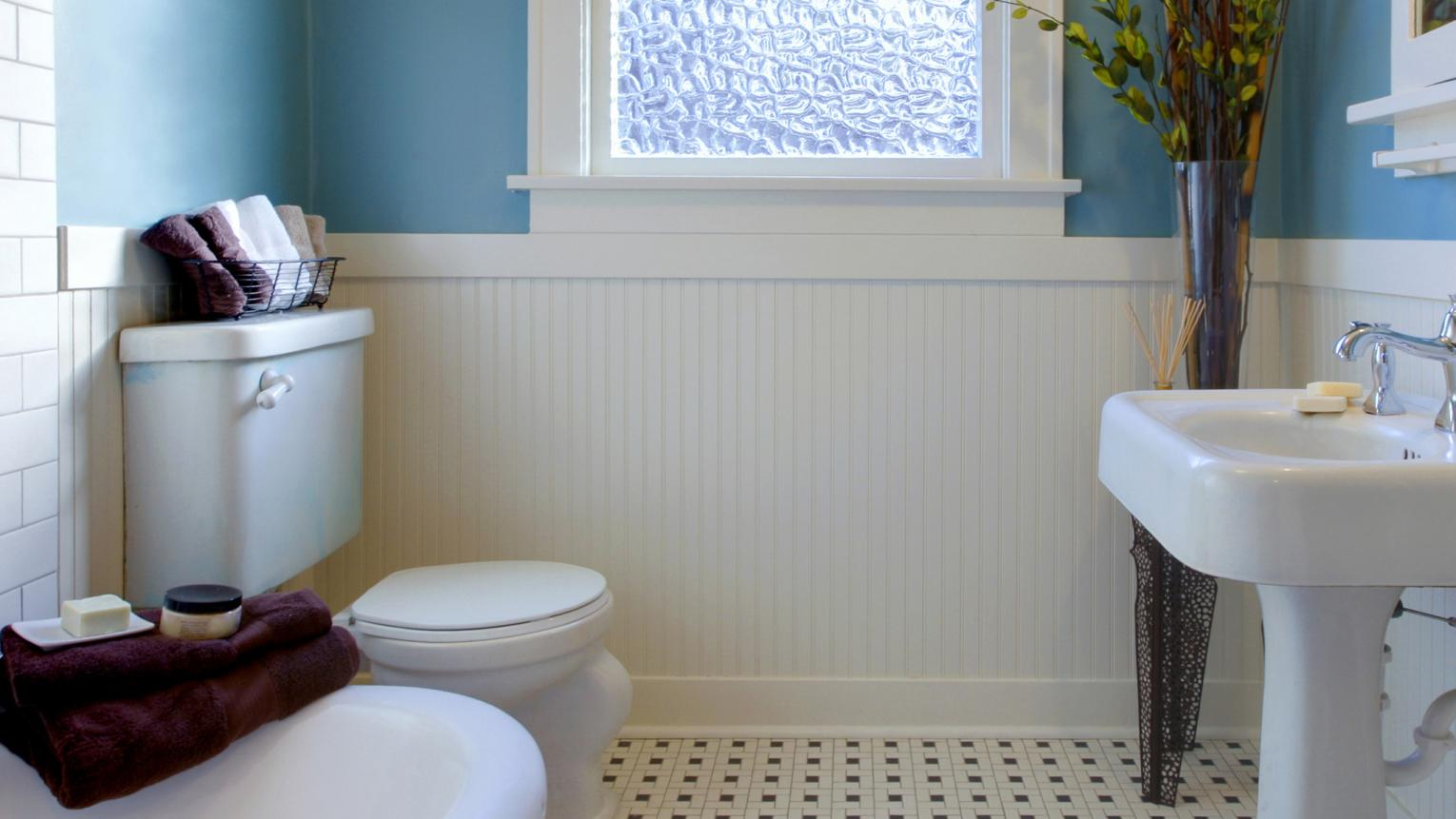 White bathroom with a blue feature wall and soft towels