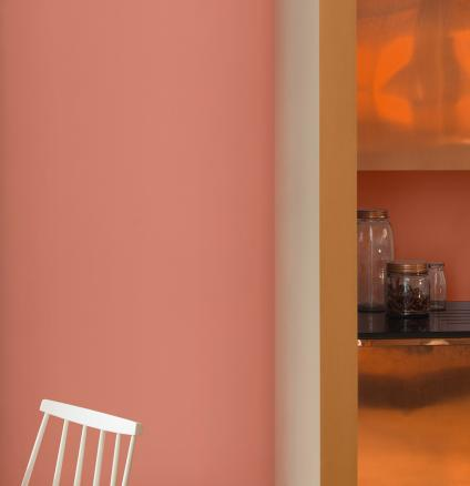 For a kitchen colour scheme guaranteed to wow your guests, pair copper orange paint with copper cabinets.